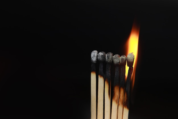 Streichhölzer, die in einer reihe von bränden in flammen stehen, sind aufeinanderfolgend, während ein streichholz vom brennen ferngehalten wird, um zu verhindern, dass sich ein feuer vor einem schwarzen hintergrund verbindet.