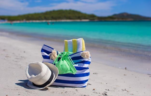 Streifentasche, strohhut, sonnencreme und frisbee auf weißem sandigem tropischem strand