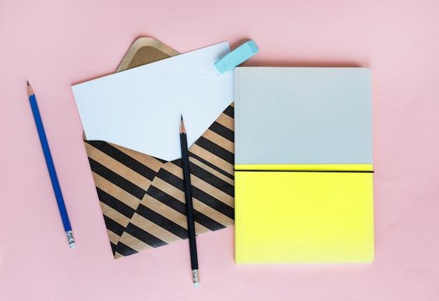 Streifenumschlag mit papier und notizbuch auf rosa hintergrund