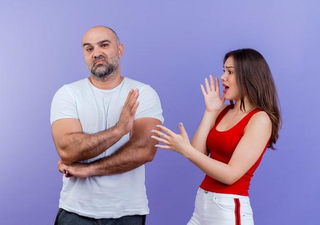 Streitende wütende frau eines erwachsenen paares, die dem mann etwas erzählt, der die hände in der luft hält, und dem unzufriedenen mann, der sie ansieht und eine stoppgeste macht