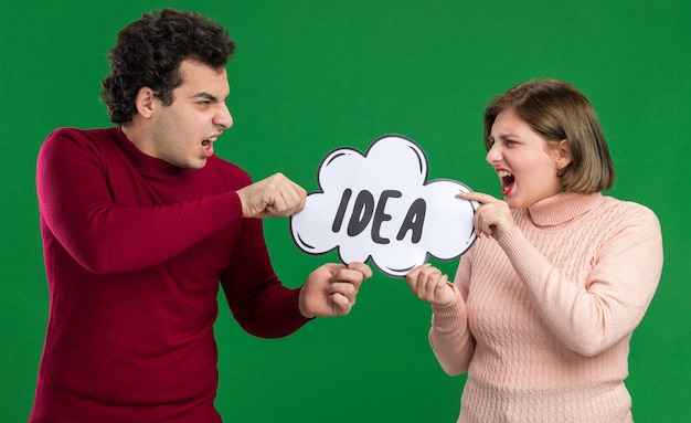 Streitendes junges paar am valentinstag, das eine ideenblase hält, die beide versucht, sie voneinander zu nehmen, isoliert auf grüner wand