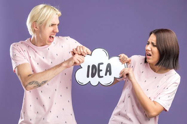 Streitendes junges paar, das pyjamas trägt und ideenblase hält, die beide daran ziehen, es voneinander zu nehmen wütender mann, der eine frau anschaut, verärgerte frau, die die ideenblase isoliert auf lila wand anschaut