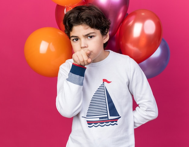 Strenge aussehende kamera kleiner junge, der vor ballons steht, zeigt vorne isoliert auf rosa wand