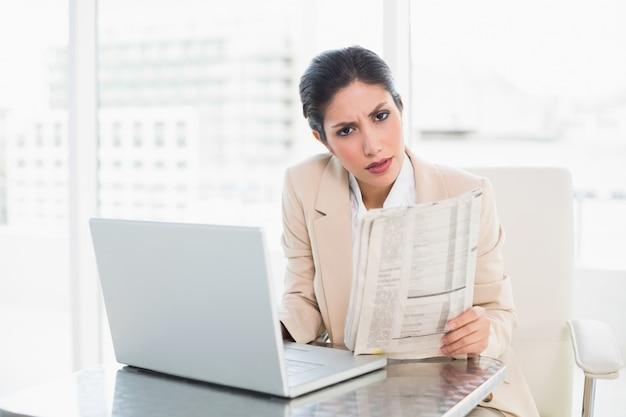 Strenge geschäftsfrau, die zeitung beim arbeiten an dem laptop betrachtet kamera hält