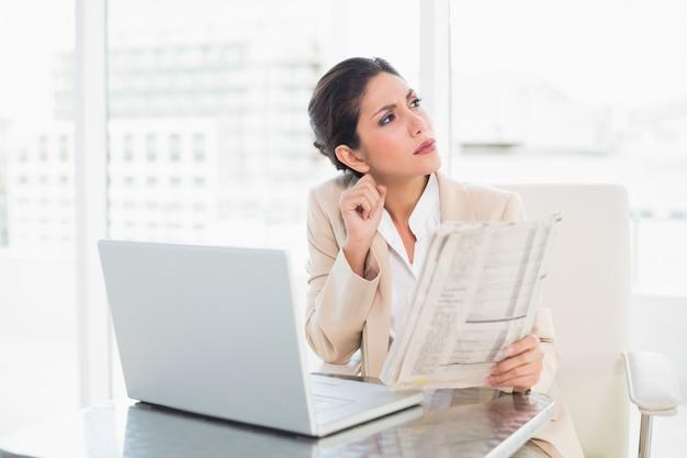 Strenge geschäftsfrau, die zeitung beim arbeiten an dem laptop weg schaut hält