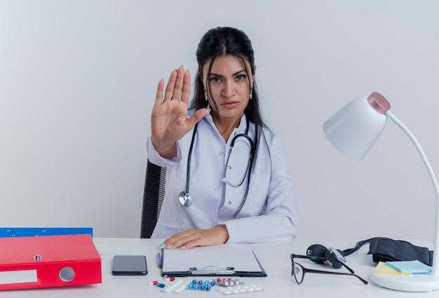 Strenge junge ärztin, die medizinische robe und stethoskop trägt, sitzt am schreibtisch mit medizinischen werkzeugen, die hand auf schreibtisch setzen und stoppgeste lokalisiert tun