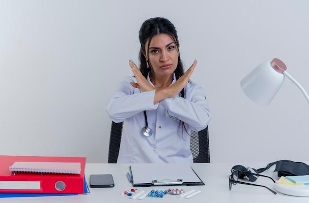 Strenge junge ärztin, die medizinische robe und stethoskop trägt, sitzt am schreibtisch mit medizinischen werkzeugen, die suchen und keine geste isoliert tun