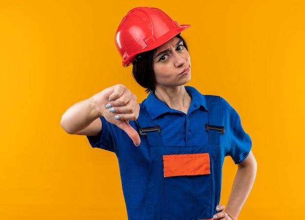 Strenge junge baumeisterin in uniform, die den daumen nach unten zeigt und die hand auf die hüfte legt, isoliert auf gelber wand