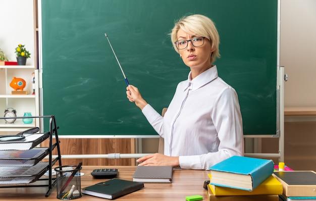 Strenge junge blonde lehrerin mit brille, die am schreibtisch mit schulmaterial im klassenzimmer sitzt und auf die tafel mit dem zeigerstock zeigt, der nach vorne schaut