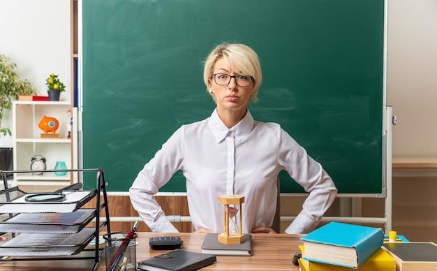 Strenge junge blonde lehrerin mit brille, die am schreibtisch mit schulmaterial im klassenzimmer sitzt und die hände auf der taille hält und nach vorne schaut