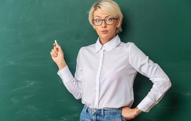 Strenge junge blonde lehrerin mit brille im klassenzimmer, die vor der tafel steht und auf die tafel zeigt, wobei kreide die hand auf der taille hält und nach vorne schaut