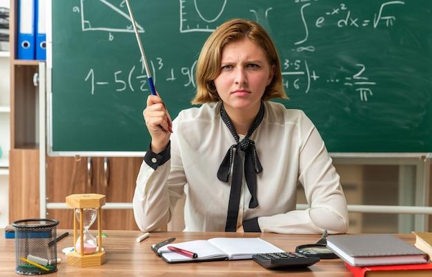 Strenge junge lehrerin sitzt am tisch mit schulmaterial, das einen zeigerstock im klassenzimmer hält