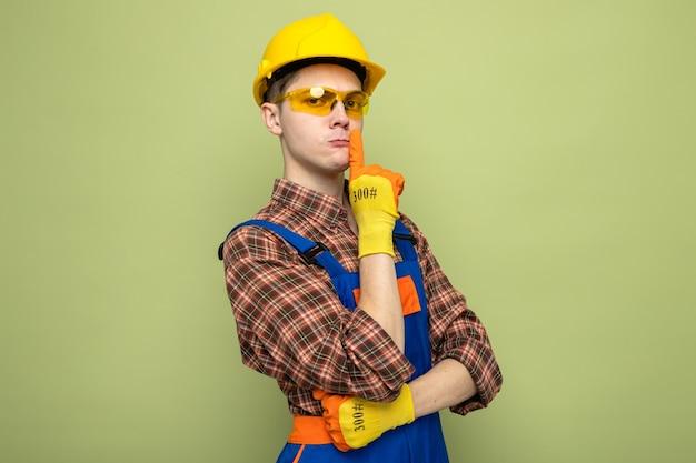 Strenge kreuzende hände, die stille zeigen, junger männlicher baumeister, der uniform und handschuhe mit brille trägt