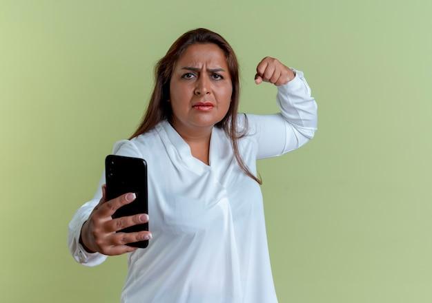 Strenge lässige kaukasische frau mittleren alters, die telefon hält und starke geste zeigt, die auf olivgrüner wand lokalisiert wird