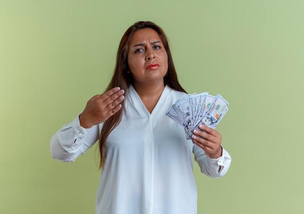 Strenge lässige kaukasische frau mittleren alters halten und zeigt mit der hand auf geld, das auf olivgrüner wand lokalisiert wird