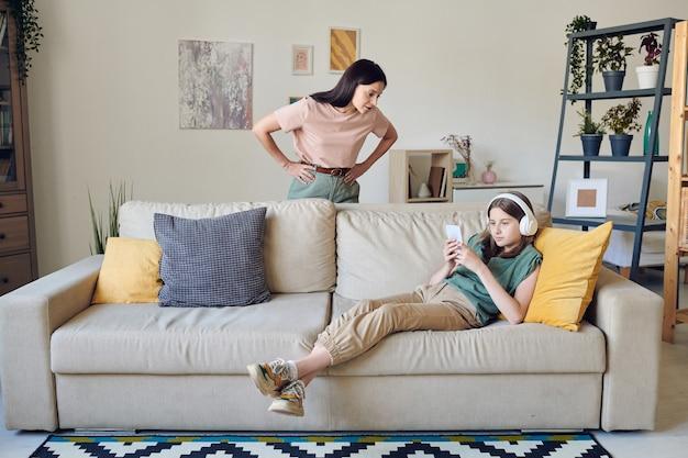 Strenge mutter, die ihre hände an der taille hält, während sie auf der couch steht, wo ihre faule teenager-tochter mit smartphone musik hört?