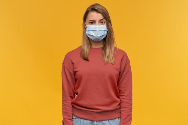 Strenge nachdenkliche junge frau im terrakotta-sweatshirt und in der kalten gesichtsmaske der medizinischen schutzgrippe mit der erhöhten stirn, die über gelber wand steht