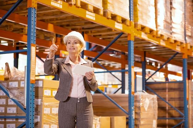 Strenge professionelle geschäftsfrau, die ein tablet hält, während sie den arbeitsprozess im lager kontrolliert