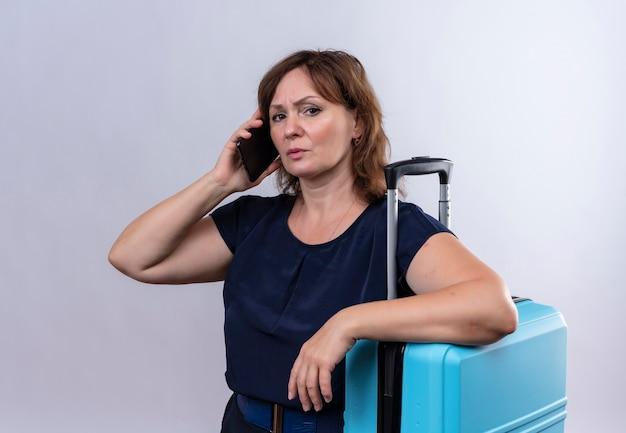 Strenge reisende mittleren alters spricht am telefon und legt hand auf koffer auf isoliertem weiß