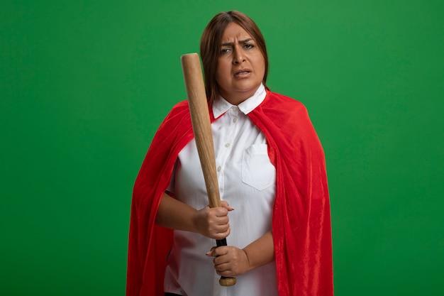 Strenge superheldenfrau mittleren alters, die baseballschläger lokalisiert auf grün isoliert