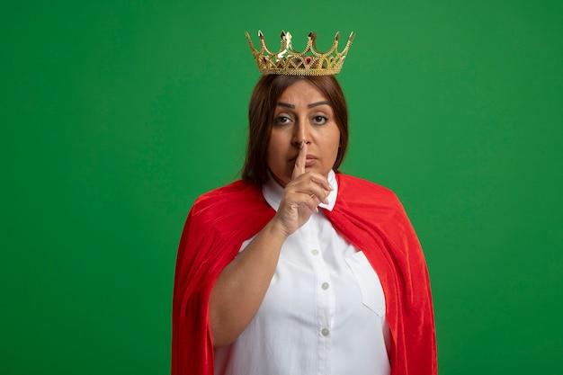 Strenge superheldenfrau mittleren alters, die krone trägt, die stille-geste zeigt, die auf grün isoliert wird