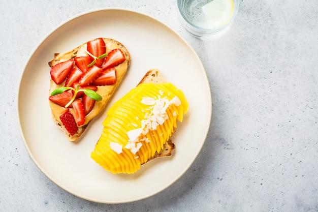 Strenge vegetarierfruchtsandwiche mit mango-, erdbeer- und erdnussbutter auf weißer platte, draufsicht.