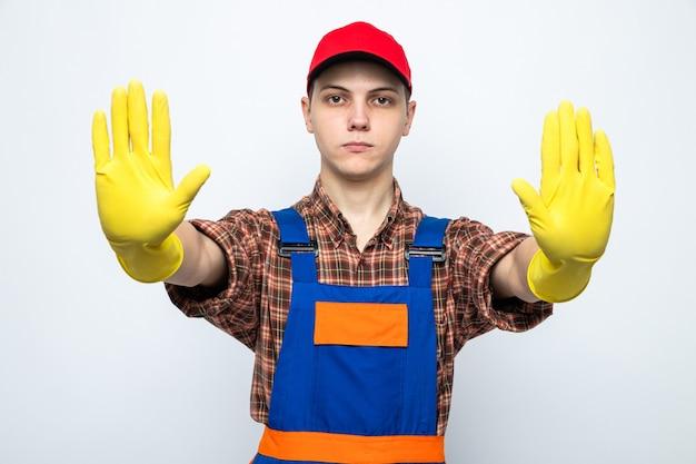 Strenge zeigende stoppgeste junger putzmann in uniform und mütze mit handschuhen