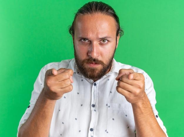 Strenger erwachsener gutaussehender mann, der die kamera anschaut und sie isoliert auf grüner wand gestikuliert?