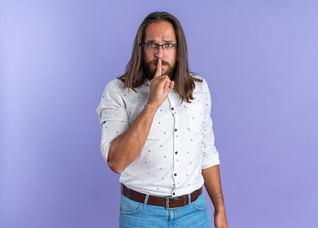 Strenger erwachsener gutaussehender mann mit brille, der die kamera anschaut und die stille-geste isoliert auf lila wand mit kopierraum macht