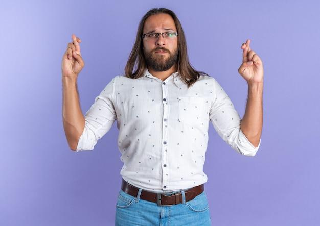 Strenger erwachsener gutaussehender mann mit brille, der die kamera anschaut und viel glück macht, isoliert auf lila wand