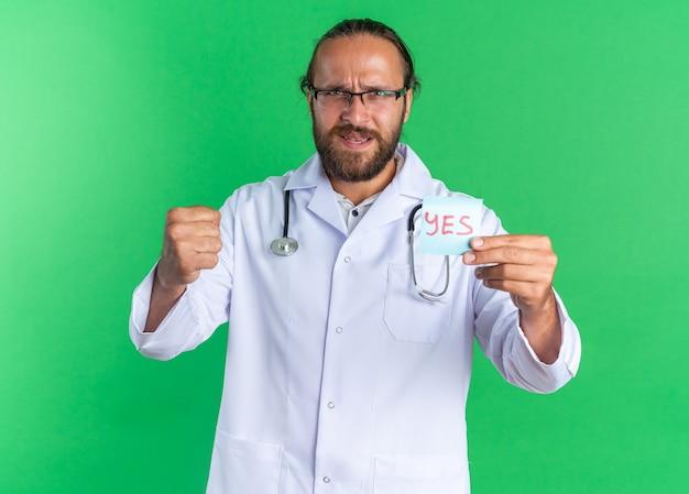 Strenger erwachsener männlicher arzt, der ein medizinisches gewand und ein stethoskop mit einer brille trägt, die eine ja-note mit blick auf die kamera zeigt, die eine starke geste isoliert auf grüner wand macht