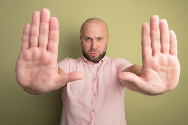Strenger glatzkopf mittleren alters, der rosa t-shirt hält hände hält