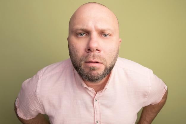 Strenger glatzkopf mittleren alters, der rosa t-shirt trägt