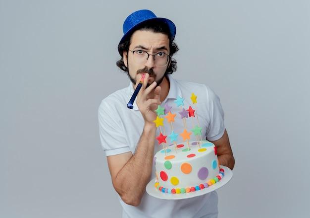 Strenger gutaussehender mann, der brille und blauen hut hält, der kuchen hält und pfeife auf weiß lokalisiert bläst