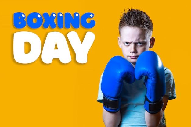Strenger junge in den blauen boxhandschuhen auf hellem gelbem hintergrund