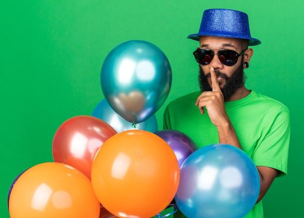 Strenger junger afroamerikanischer mann mit partyhut und brille mit ballons, die eine ja-geste einzeln auf grüner wand zeigen