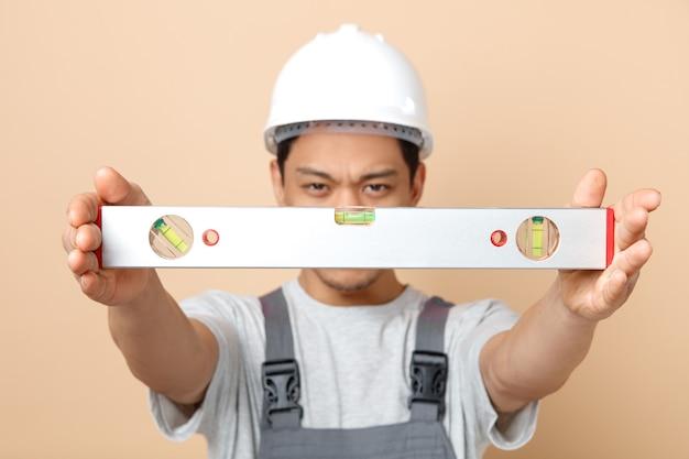 Strenger junger bauarbeiter, der schutzhelm und uniform trägt, streckt ebenes lineal in richtung kamera aus