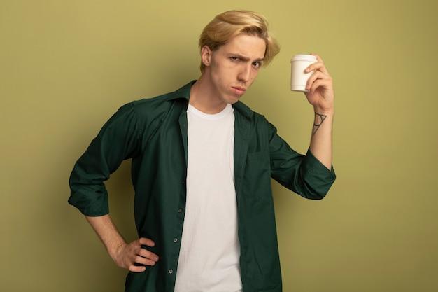Strenger junger blonder kerl, der grünes t-shirt trägt, das tasse kaffee hält und hand auf hüfte legt
