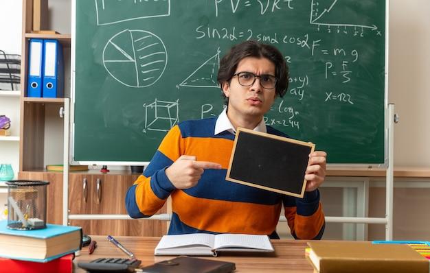 Strenger junger geometrielehrer mit brille, der am schreibtisch mit schulmaterial im klassenzimmer sitzt und eine mini-tafel zeigt, die auf die vorderseite zeigt
