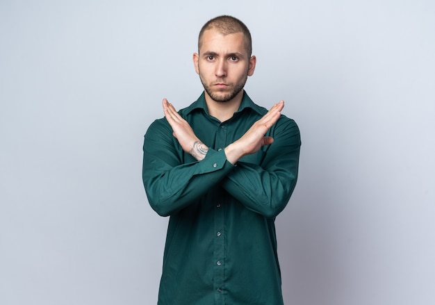 Strenger junger gutaussehender kerl, der ein grünes hemd trägt und eine geste des neins zeigt