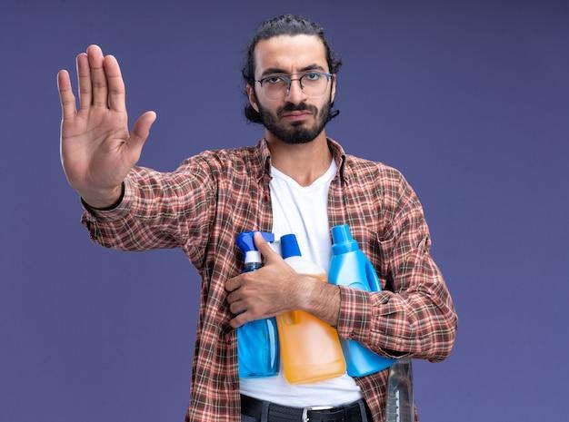 Strenger junger, gutaussehender putzmann mit t-shirt, der reinigungswerkzeuge hält, die hand an der kamera isoliert auf blauer wand halten
