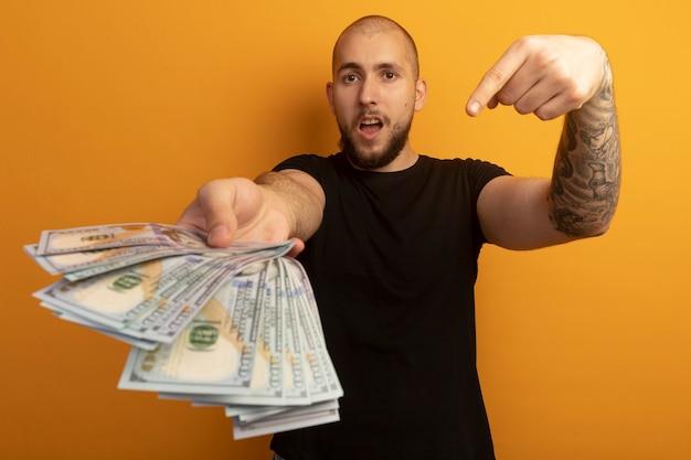 Strenger junger hübscher kerl, der schwarzes hemd hält und auf bargeld zeigt
