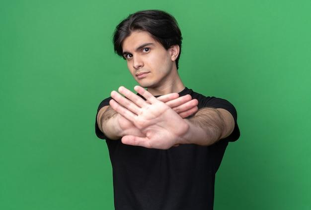 Strenger junger hübscher kerl, der schwarzes t-shirt trägt, das geste des nicht-isolierens auf grüner wand zeigt
