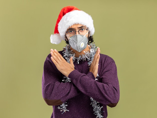 Strenger junger hübscher kerl, der weihnachtshut und medizinische maske mit girlande am hals trägt, zeigt geste von nicht isoliert auf olivgrünem hintergrund