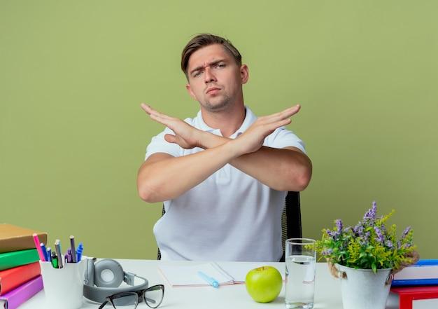 Strenger junger hübscher männlicher student, der am schreibtisch mit schulwerkzeugen sitzt, die geste des nein auf olivgrün zeigen