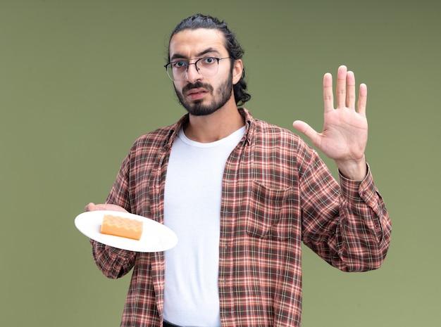 Strenger junger hübscher reinigungsmann, der t-shirt trägt, das schwamm auf platte hält, die stoppgeste zeigt, die auf olivgrüner wand lokalisiert wird