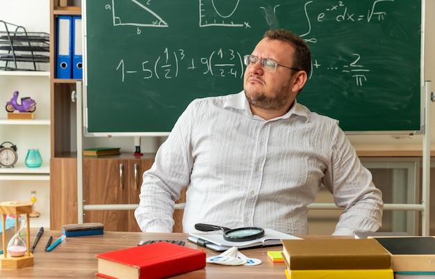 Strenger junger lehrer mit brille, der am schreibtisch mit schulmaterial im klassenzimmer sitzt und die hand auf der taille hält und zur seite schaut