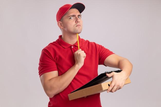 Strenger junger lieferbote, der uniform mit kappe trägt, die klemmbrett mit pizzaschachtel hält und bleistift auf kinn lokalisiert auf weißer wand setzt