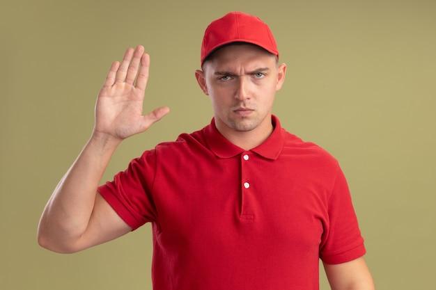 Strenger junger lieferbote, der uniform und kappe trägt, die stoppgeste zeigt, die auf olivgrüner wand lokalisiert wird