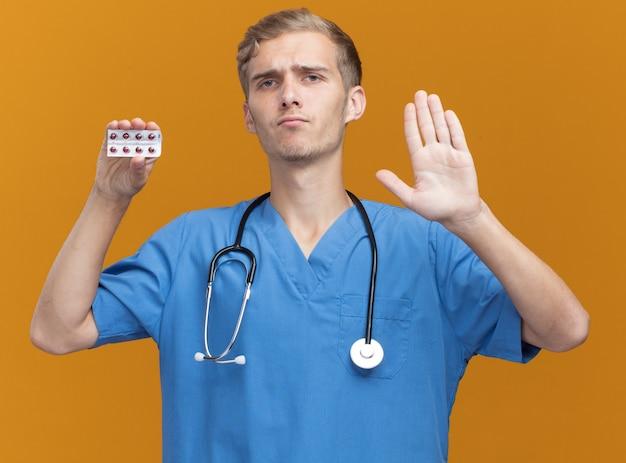 Strenger junger männlicher arzt, der arztuniform mit stethoskop hält, das pillen hält, die stoppgeste zeigen, die auf orange wand lokalisiert wird